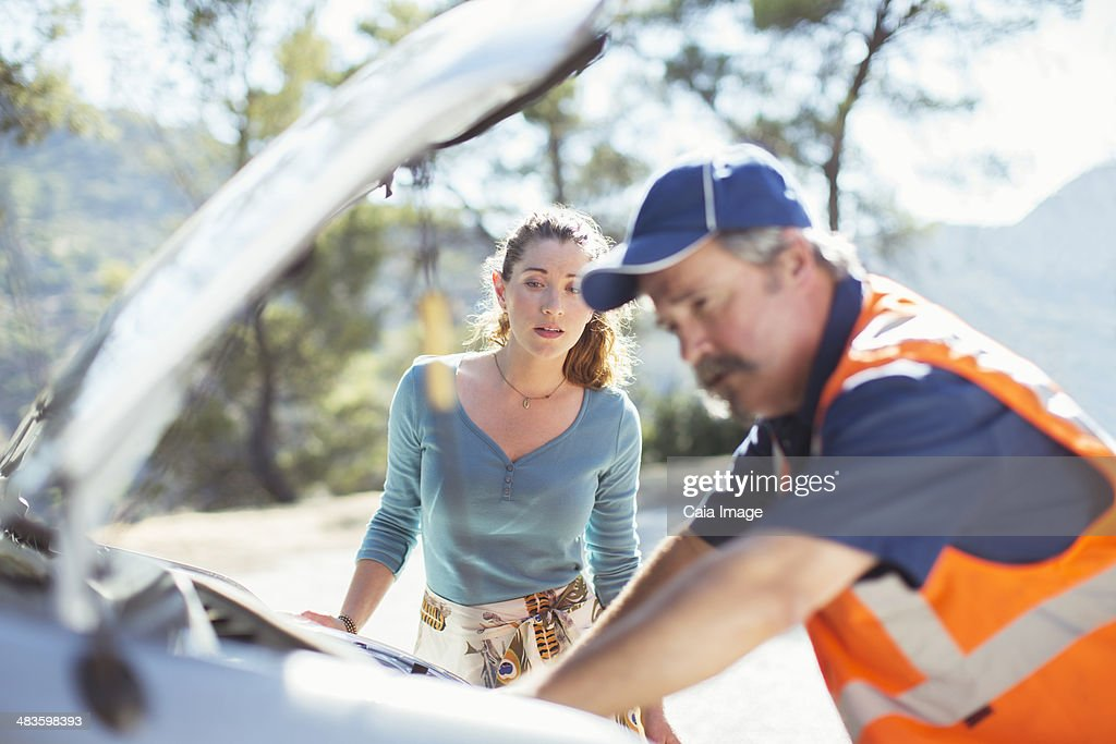 Woman watching roadside mechanic check car engine