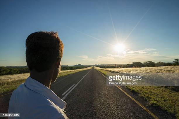Woman watching sun setting on an empty road