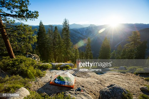 A woman watching sunrise from a tent.