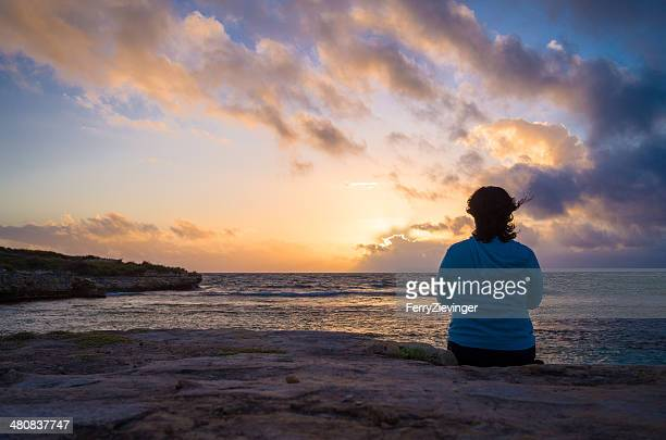 Antigua and Barbuda, Woman watching sunrise near Devil's Bridge