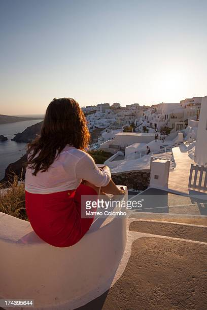 Woman watching sunset over town of Oia Santorini