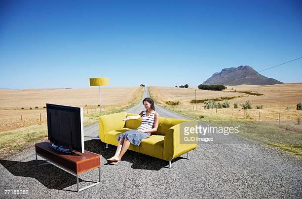 Une femme regardant la télévision sur un canapé à la route