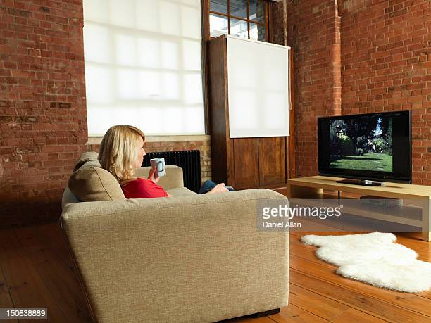 Woman watching television on sofa