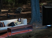 A woman watching television outdoors in the woods