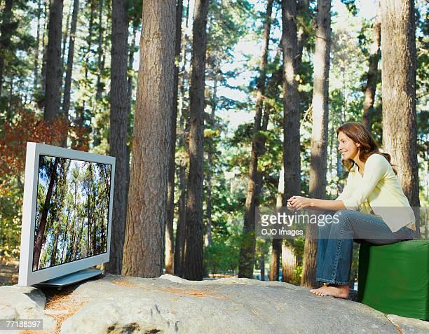 Eine Frau vor dem Fernseher im Freien im Wald