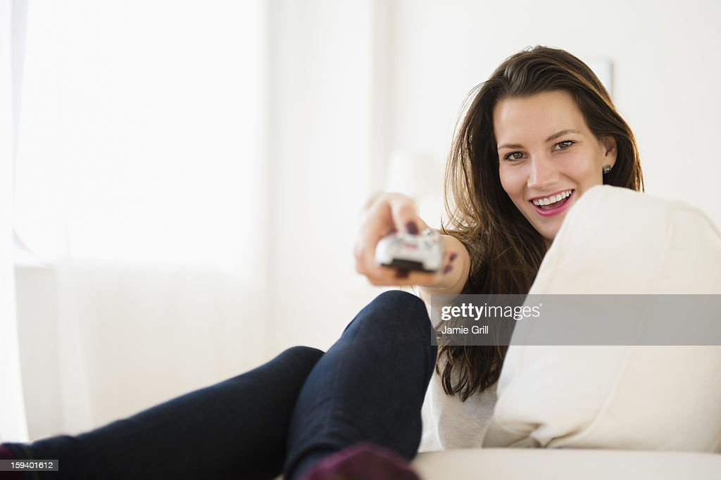 Woman watching television, smiling : Stock Photo