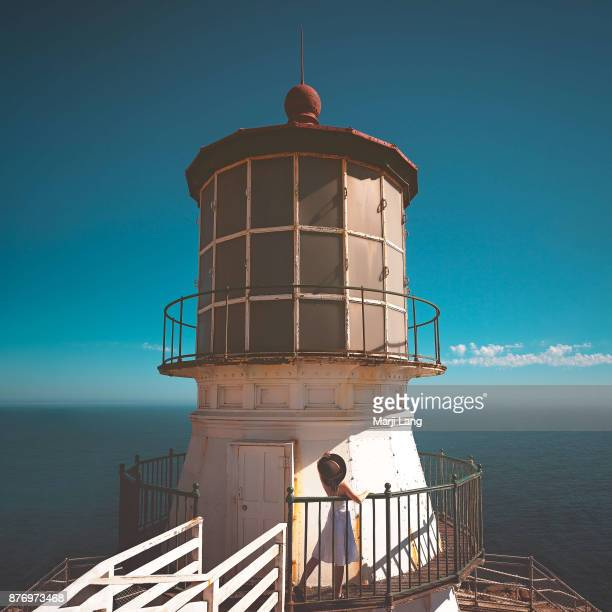 Woman watching the Pacific ocean at Point Reyes lighthouse in California USA