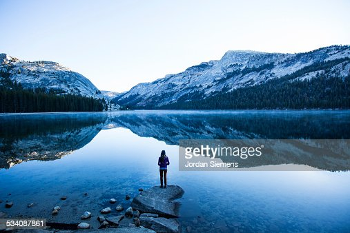 A woman watching the sunrise over a lake.