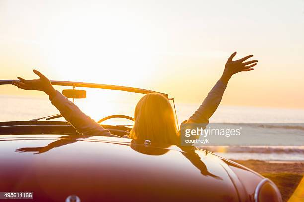 Woman watching the sunset in a convertible car.