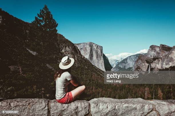Woman watching the Yosemite valley from the Tunnel view in Yosemite National Park California USA