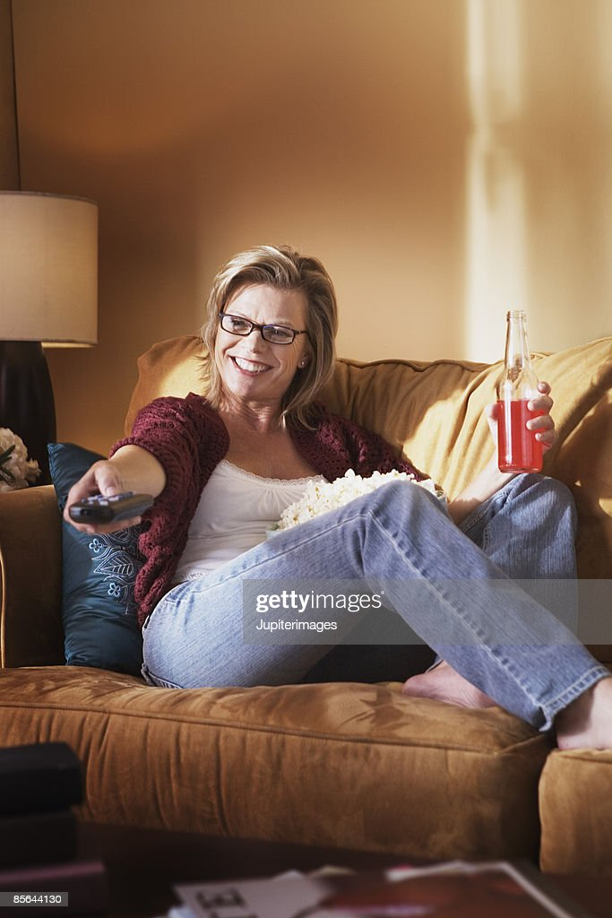 Woman watching TV with popcorn and soda : Stock Photo
