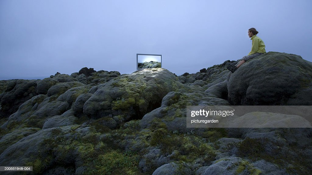 Woman watching wide screen television on rock, side view : Stock Photo