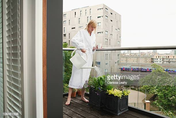 Woman watering flowers on balcony
