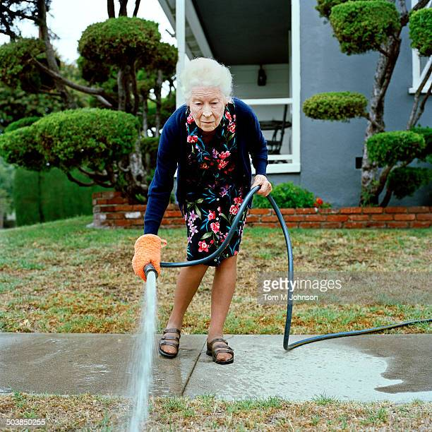 Woman watering her front lawn