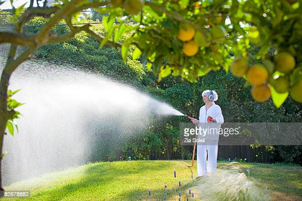 woman watering lawn with headphones on