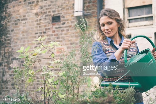Woman watering plants in her urban garden (London, UK).