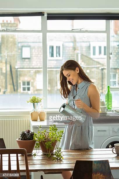 Frau gießen Pflanzen