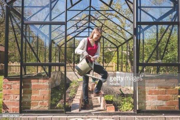 Frau, Bewässerung von Pflanzen stehen im Gewächshaus gegen blauen Himmel