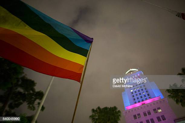 A woman waves a flag near City Hall which is lit in the colors of the rainbow flag to honor the LGBT victims of the worst mass shooing in United...