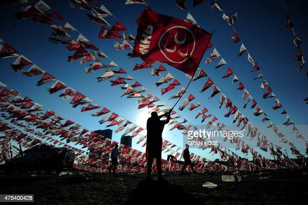 A woman waves a flag of Turkeys Nationalist Movement Party during an election campaign rally on May 31 2015 at Kazlicesme neighborhood in Istanbul...