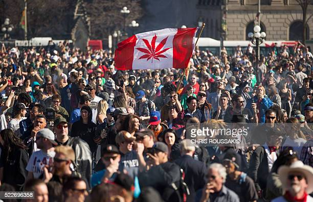 A woman waves a flag with a marijuana leaf on it during a rally to celebrate National Marijuana Day on Parliament Hill in Ottawa Canada on April 20...
