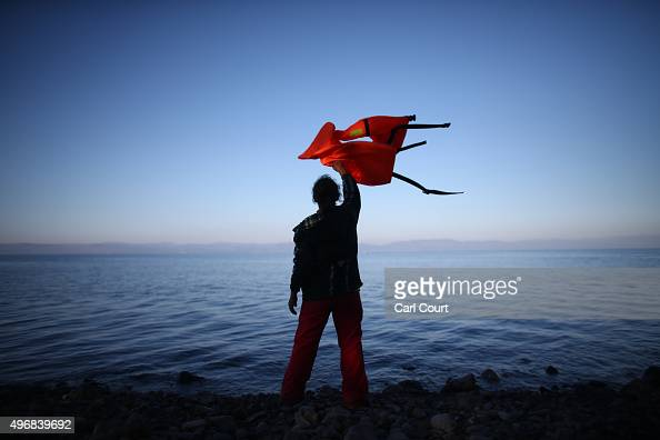 A woman waves a life jacket to direct a migrant boat ashore as it makes the crossing from Turkey to the Greek island of Lesbos on November 12 2015 in...
