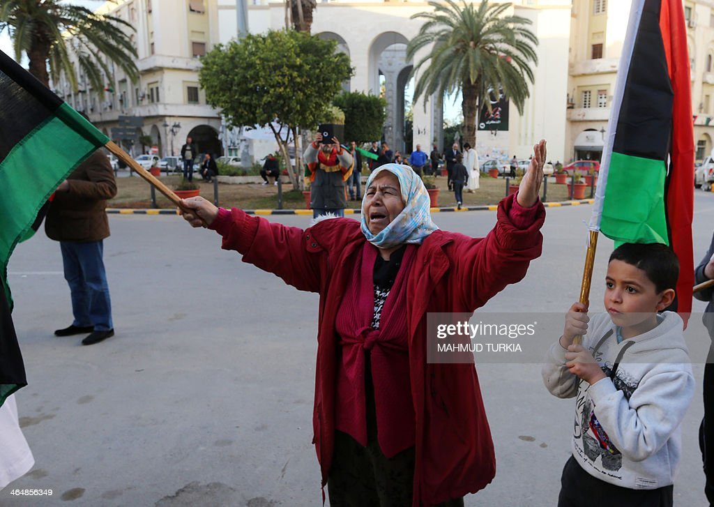 A woman waves a national flag during a protest against the latest bloody clashes in the south of the country on January 24, 2014 in Algeria square in the Libyan capital Tripoli. Violence in Libya killed 643 people last year, amid a sharp rise in crime, according to a parliamentary report that laments a lack of effective policing in the increasingly lawless North African country.