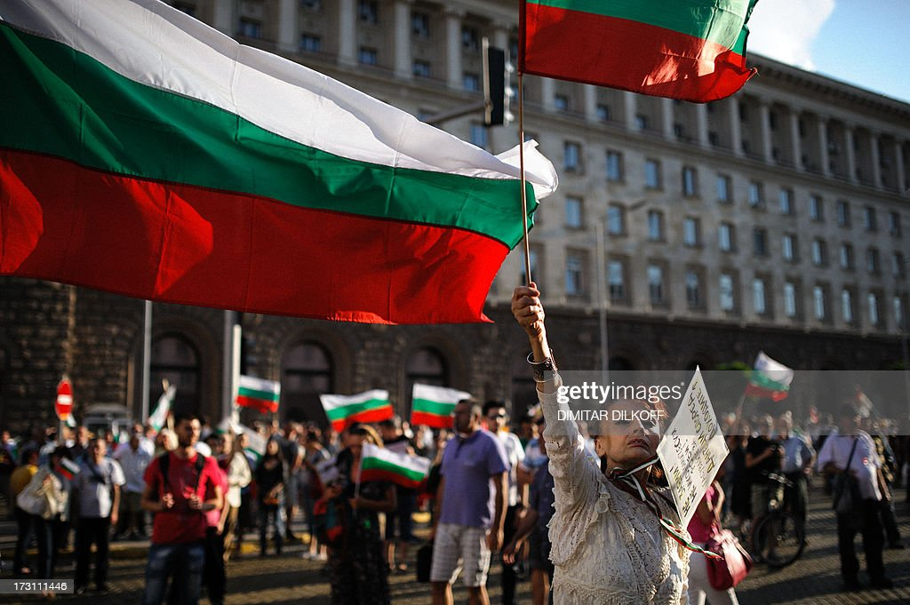 A woman waves a national flag on July 7, 2013 during an anti-government protest in Sofia. Thousands of Bulgarians have joined nightly rallies in Sofia and other towns since June 14, just months after anti-poverty and corruption demonstrations forced out the previous conservative government in February. AFP PHOTO / DIMITAR DILKOFF