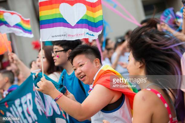 A woman waves a pride flag as she marches in the Pride Parade in Toronto Ontario June 25 2017 The event draws hundreds of thousands of spectators...