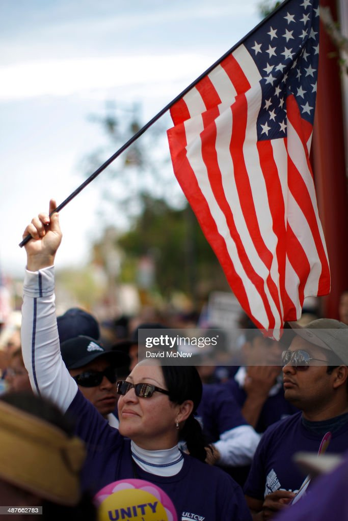 A woman waves an American flag as people rally before marching to the Metropolitan Detention Center during one a several May Day immigrationthemed...