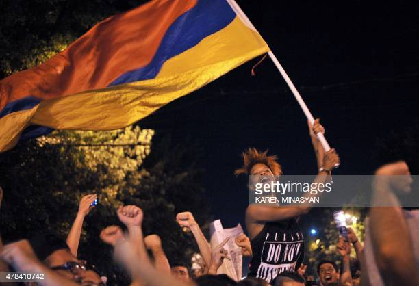 A woman waves an Armenian flag as thousands of protesters block a street during a demonstration against an increase of electricity prices in Yerevan...