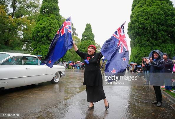 A woman waves Australian flags as she shows her support for people taking part in the Anzac Day March on ANZAC Day at the Shrine of Remembrance on...