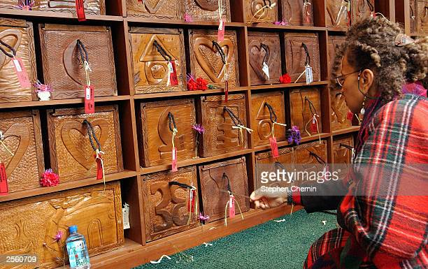 A woman waves incense in front of hand carved caskets at the African Burial Ground during a reinternment ceremony October 4 2003 in New York City...
