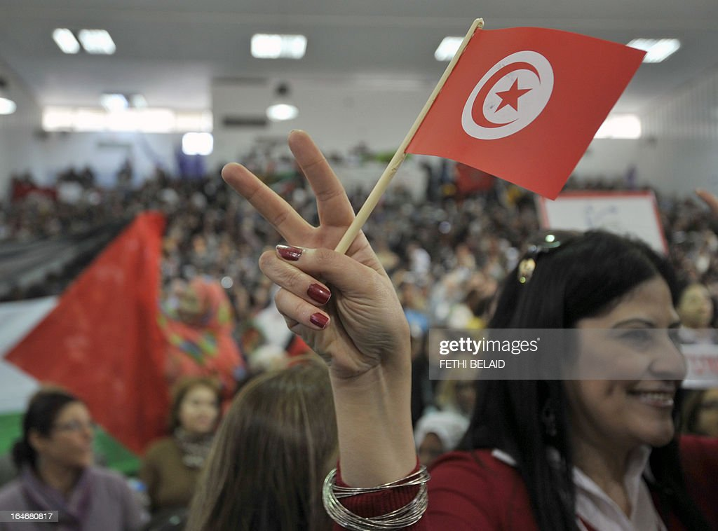 A woman waves the Tunisian flag as she flashes the sign for victory at the opening of the World Social Forum (WSF) on March 26, 2013, in Tunis. More than two years after the Jasmine revolution, tens of thousands of people are expected for the WSF, dubbed the forum of 'dignity', a watchword of the Tunisian uprising that inspired revolts across the Arab world.