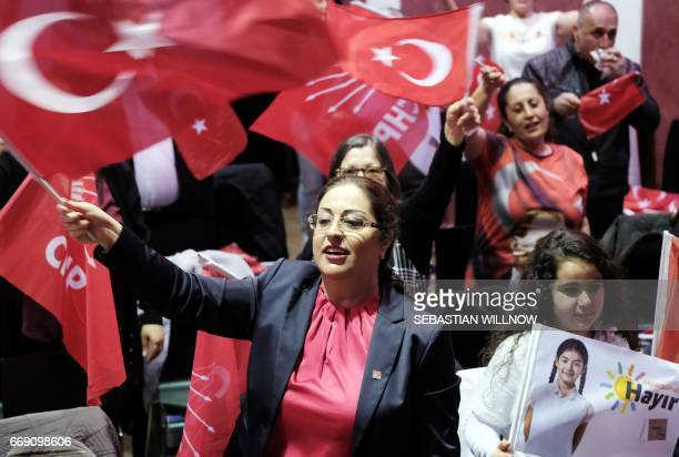 A woman waves the Turkish flag during an election party of the Republican People's Party in Berlin on April 16 2017 Turkey voted Sunday to decide...