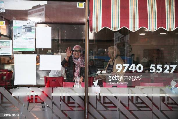 A woman waves through her shop window in the southwestern suburb of Lakemba on May 27 2017 in Sydney Australia Muslims around the world mark the...