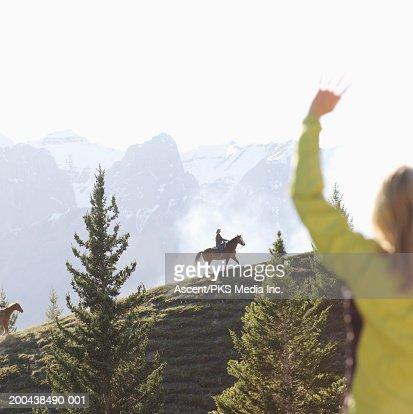 Woman waving at people horseback riding in mountains at sunset : Stock Photo