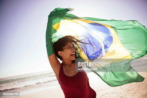 Woman waving brazilian flag on beach