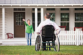 Woman waving from their home to her husband in a wheelchair with a spinal cord injury