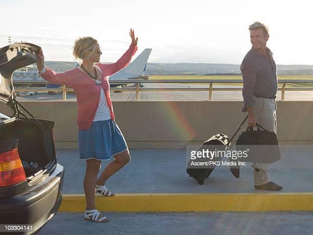 Woman waving goodbye to man at airport