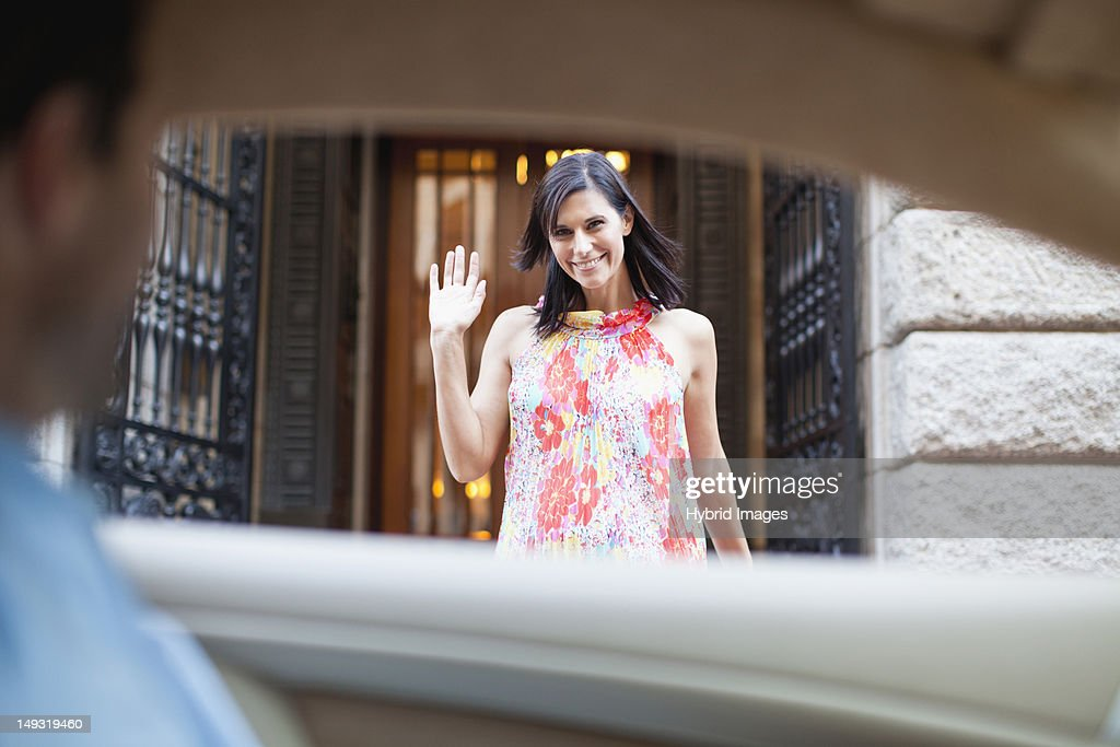 Woman waving to boyfriend in car
