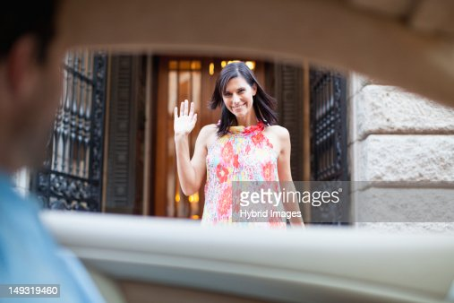 Woman waving to boyfriend in car