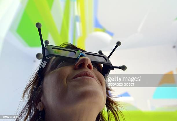 A woman wearing 3D glasses tests a Cave Automatic Virtual Environment virtual reality theatre during its presentation at the Industrial Centre for...