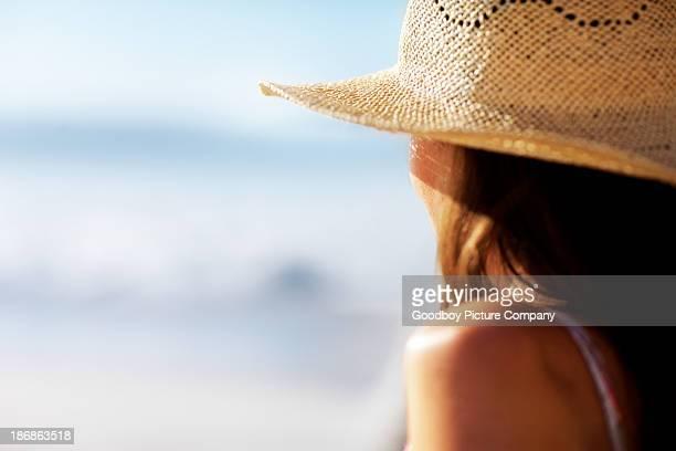 Woman wearing a beach hat against calm sea