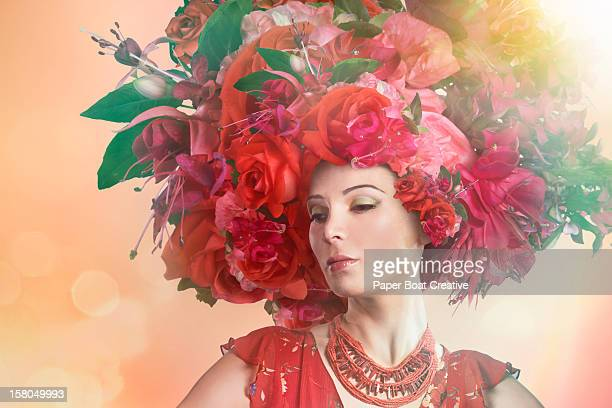 Woman wearing a big red hat made of roses