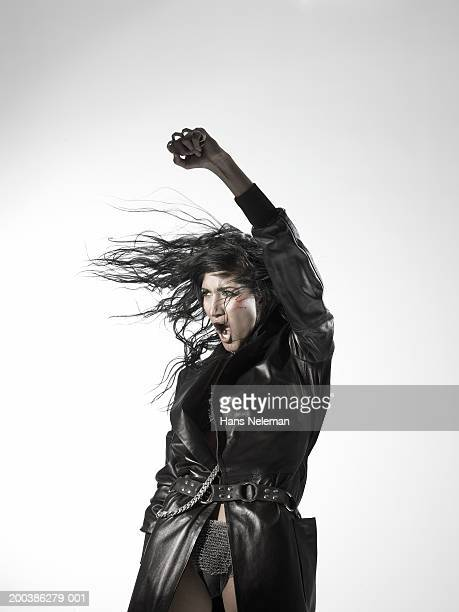 Woman wearing a black leather trench coat, shouting, left arm raised