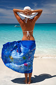 rear view of woman wearing blue sarong on a tropical beach