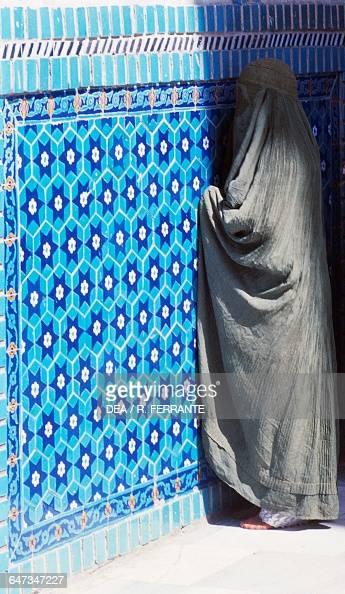 Woman wearing a burqa in prayer Shrine of Ali or Blue Mosque Mazare Sharif Afghanistan