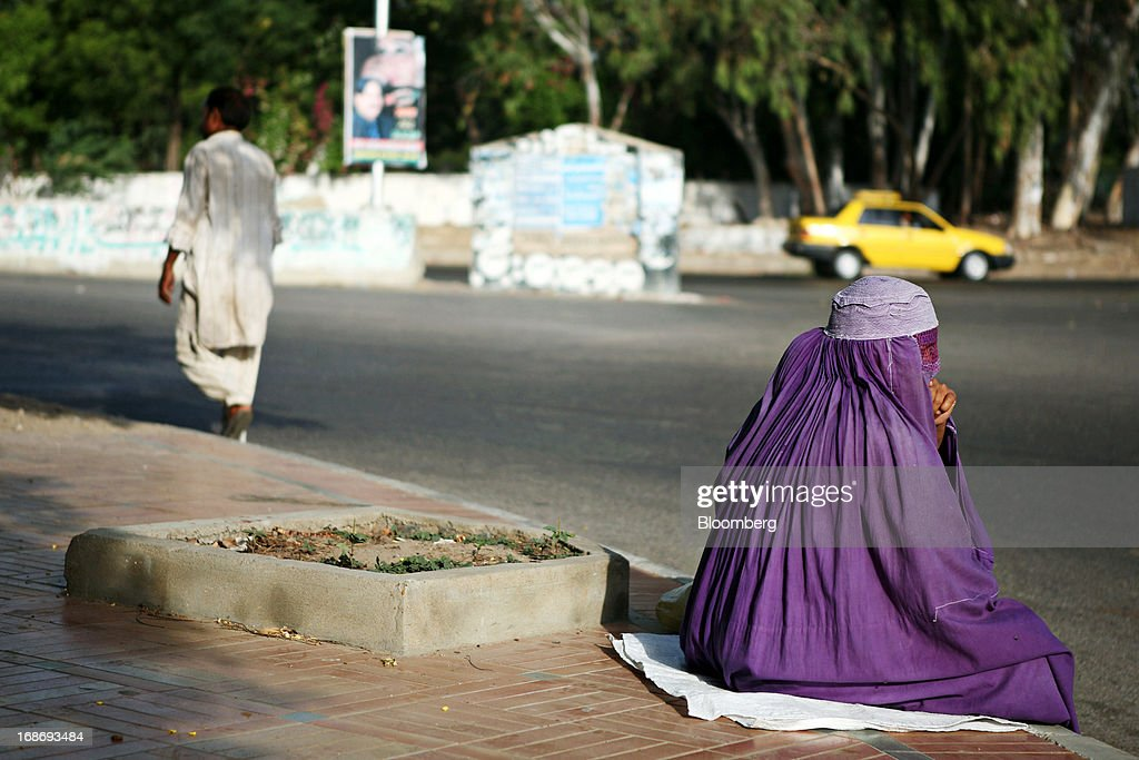 A woman wearing a burqa sits on a sidewalk in Karachi, Pakistan, on Monday, May 13, 2013. Nawaz Sharif was headed for a record third term as prime minister of Pakistan as unofficial results from a landmark election gave him the convincing win he sought to tackle a slumping economy and growing militancy. Photographer: Asim Hafeez/Bloomberg via Getty Images