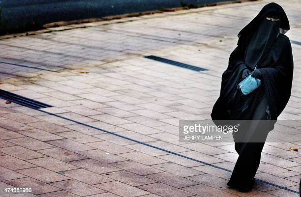 A woman wearing a burqa walks in The Hague on December 1 2014 The Dutch cabinet approved on May 22 2015 a partial ban on wearing the facecovering...
